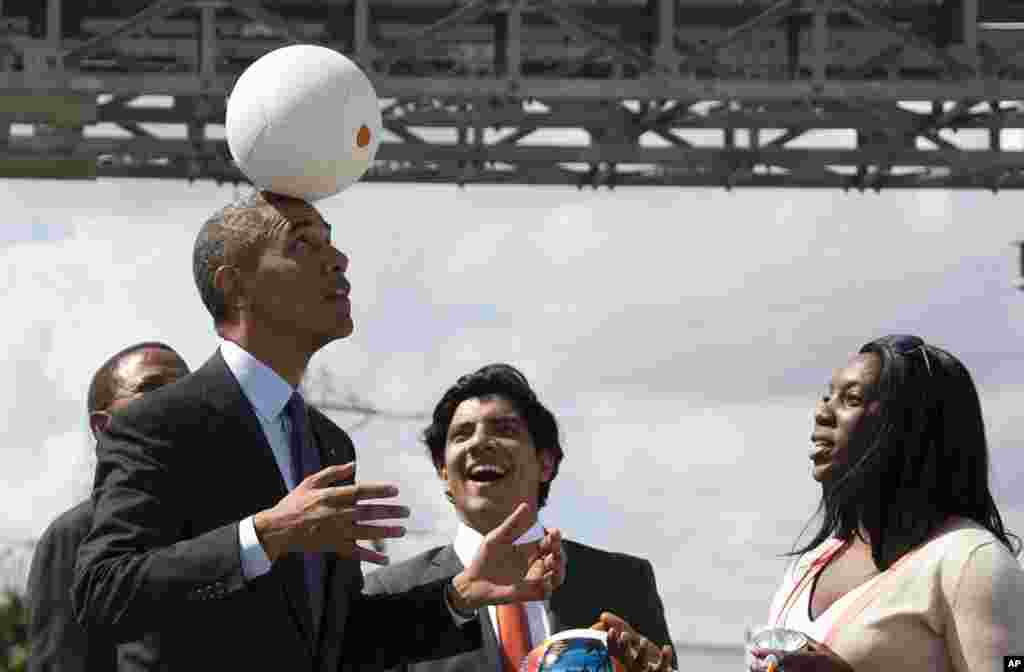 "U.S. President Barack Obama demonstrates ""the Soccket Ball,"" which uses kinetic energy to provide power to charge a cell phone or power a light, during an event at the Ubungo power plant to promote energy innovation in Dar Es Salaam, Tanzania."