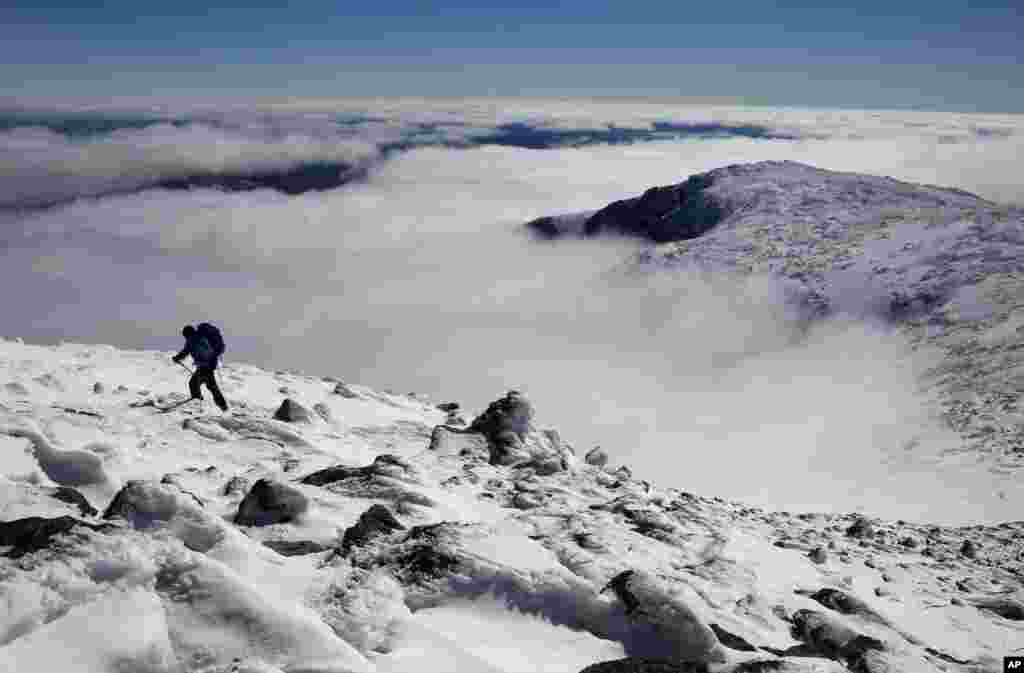 Clouds fill Tuckerman Ravine below Peter Arthur as he makes the final push to the summit of 1,917-meter Mount Washington in New Hampshire.