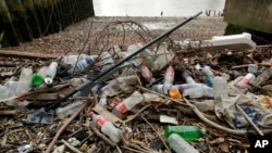 Des bouteilles en plastique et d'autres plastiques, dont une vadrouille, reposent sur la rive nord de la Tamise à Londres le 5 février 2018. (AP Photo/Matt Dunham, dossier)