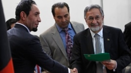 Afghanistan's former Foreign Minister Zalmay Rassoul (R) receives a form to register as a candidate for the presidential election at Afghanistan's Independent Election Commission (IEC) in Kabul October 6, 2013.