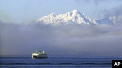 A Washington state ferry emerges from a fog bank on Puget Sound near Bainbridge Island in this 2013 file photo.