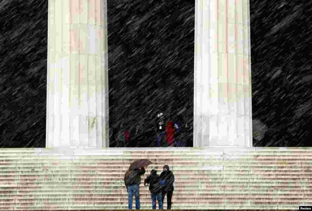 Tourists brave the falling snow to visit the Lincoln Memorial in Washington, March 6, 2013.