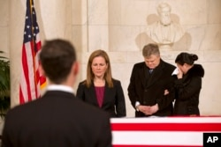 A woman cries as friends and staff of the Supreme Court attend a private ceremony in the Great Hall of the Supreme Court where late Supreme Court Justice Antonin Scalia lies in repose, Feb. 19, 2016, in Washington.