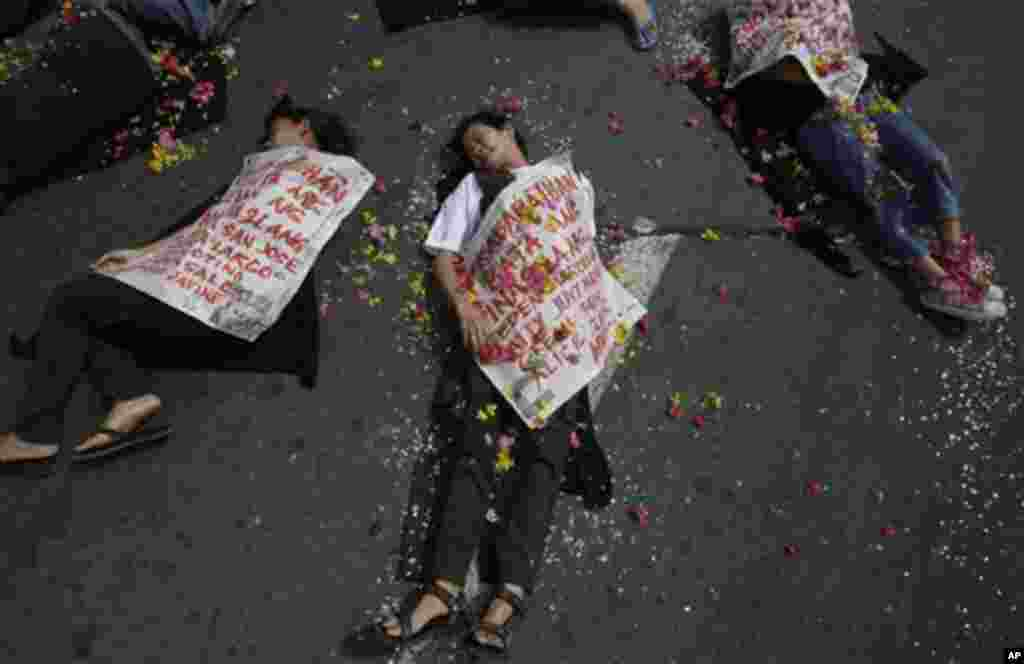 Filipino women activists stage a play to symbolize human rights violations during a demonstration to mark the International Day of Action on Violence Against Women near the Malacanang presidential palace in Manila, Philippines, Friday Nov. 25, 2011. The w