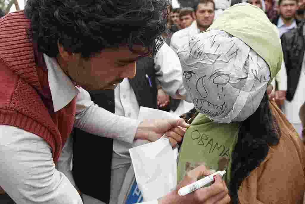 Seorang demonstran menuliskan kata-kata di boneka yang melambangkan Presiden Obama dalam sebuah aksi protes di Jalalabad (AP).