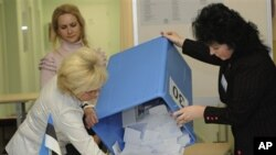 Estonian election commission staff members open a ballot box at a polling station after the parliamentary elections closed in Tallinn, Estonia, on Sunday, March 6, 2011.