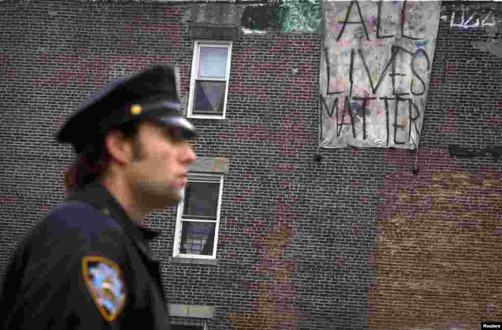 """Một sĩ quan cảnh sát đứng ở phía trước của một biểu ngữ viết """"Mọi mạng sống đều quan trọng"""" treo trên một tòa nhà bên kia con đường, nơi hai sĩ quan cảnh sát bị bắn chết tại quận Brooklyn của thành phố New York, ngày 22 tháng 12, 2014."""