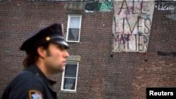 """Un oficial de policía frente a un cartel que dice """"Todas las vidas importan"""" en Brooklyn."""