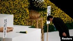 15일 일본 도쿄 부도칸 홀에서 열린 세계2차대전 폐전 69주년 기념식에서 아베 신조 일본 총리가 전사자들에게 헌화한 후 절하고 있다. 아베 초리는 또한 야스쿠니 신사에 공물료를 납부했다.
