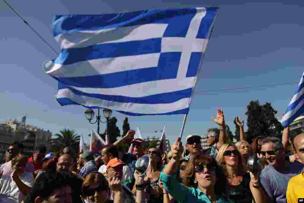 Protesters wave Greek flags outside the Greek parliament during a protest at the 24-hour nationwide general strike in Athens, October 18, 2012.