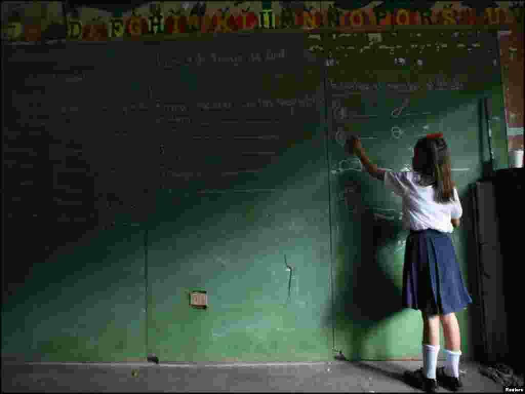 مناگوا کے ایک ایلیمینٹری اسکول میں طالبہ چاک کی مدد سے بورڈ پر لکھ رہی ہے۔