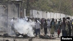 Residents gather at the scene of a suicide attack along a street in Somalia's capital Mogadishu October 4, 2011.