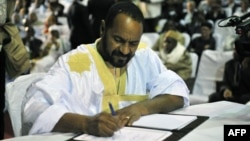 FILE - Sidi Brahim Ould Sidati, a member of the Arab Movement of Azawad, signs the peace accord on behalf of the Coordination of Azawad Movements in Bamako, Mali, June 20, 2015.