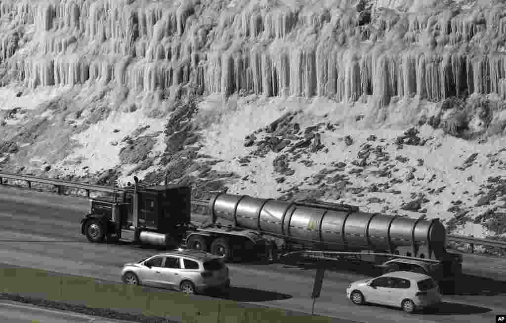 Traffic moves south on I-75 past a hill covered with ice in Covington, Kentucky, USA, where temperatures remain in single digits.