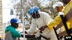 Une infirmière prend soin d'un patient atteint de choléra lors d'une visite du ministre de la Santé du Zimbabwe, au centre de traitement du choléra de l'hôpital Beatrice, à Harare, le 11 septembre 2018.