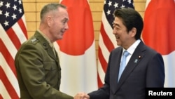 General Joseph Dunford, left, the chairman of the U.S. Joint Chiefs of Staff, shakes hands with Japan's Prime Minister Shinzo Abe at Abe's official residence in Tokyo, Japan, Aug. 18, 2017.