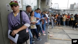 FILE - Venezuelan citizens stand in a line outside the Foreign Ministry office in Lima, Peru, Jan. 23, 2018.