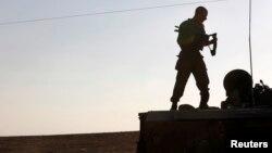 Binh sĩ Israel đứng trên xe bọc thép gần biên giới dải Gaza.