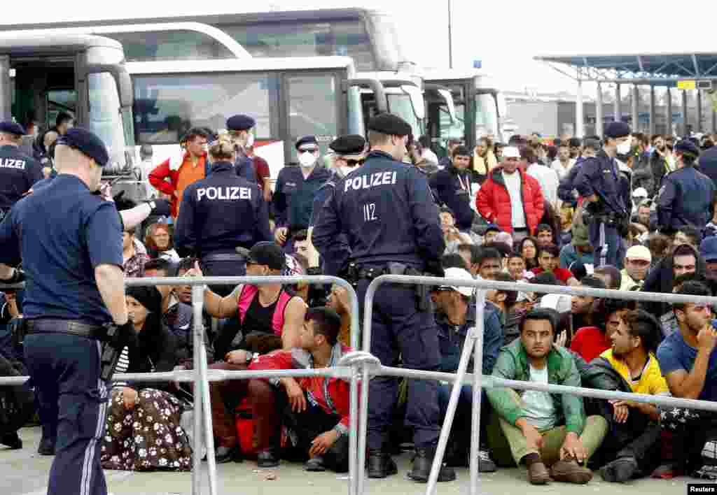 Migrants wait to board busses in Nickelsdorf, Austria. Thousands of migrants walked unhindered across the border into Austria from Hungary, where the frontier was kept open despite Germany's sudden reintroduction of checks.