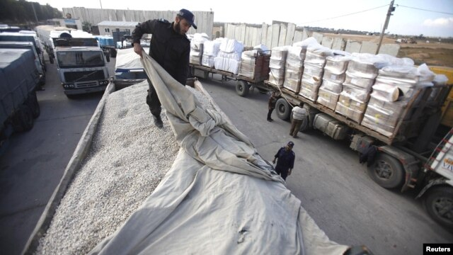 A member of Hamas security forces checks a truck loaded with gravel at the Kerem Shalom crossing between Israel and the southern Gaza Strip, December 30, 2012.