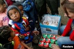 Dete iz Venecuele čeka hranu u redu za migrante u improvizovanom kampu blizu Bogote u Kolumbiji, 5. septembra 2018.
