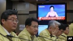 韩国外交部官员举行紧急会议,旁边的电视播放着朝鲜宣布核试验的新闻(2016年1月6日)
