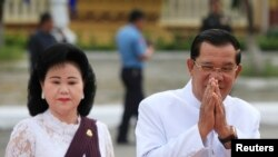 FILE - Cambodia's Prime Minister Hun Sen (R) and his wife Bun Rany arrive at the Royal Palace during commemorations for the second anniversary of late king Norodom Sihanouk's death, in Phnom Penh.