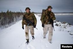 Patrol leader Joergen Aas (L) and radio operator Thomas Lundmann patrol the Norwegian side of the Norway-Russia border in Pasvik valley, Finnmark county, Norway, Oct. 23, 2019.