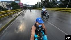 Manuel Mendoza viaja en su silla de ruedas agarrándose a la parte trasera de una motocicleta en el barrio La Paz de Caracas, el 9 de noviembre de 2020.