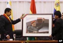 El presidente de Venezuela, Nicolás Maduro, a la izquierda, le entrega una fotografía del difunto presidente Hugo Chávez al presidente de Bolivia, Evo Morales, en una reunión en Cochabamba, Bolivia. Mayo 25, 2013. Foto: AP.