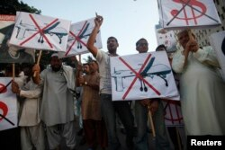 FILE - Protesters hold placards as they shout anti-American slogans during a protest against U.S. drone attacks in Karachi, Oct. 23, 2013.