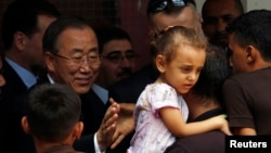 United Nations chief Ban Ki-moon greets a Palestinian man, whose house was destroyed, at a UN-run shelter for Gaza City refugees on Oct. 14, 2014.