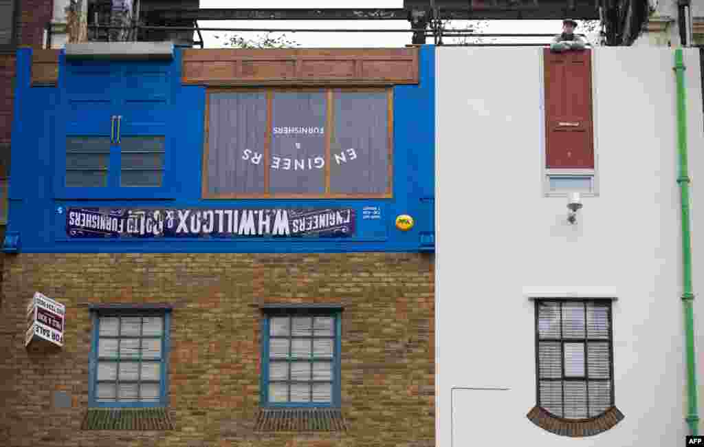 Artist Alex Chinneck poses on the rooftop of his latest art installation Miner on the Moon (Upside Down House) upon its unveiling on Blackfriars Road in Central London.