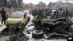ຜູ້ຄົນຫຸ້ມເບິ່ງລົດທີ່ໄດ້ຮັບຄວາມເສຍຫາຍຈາກເຫດລະເບີດທີ່ຖະໜົນ al-Thawra ໃນກຸງ Damascus (5 ພຶດສະພາ 2012)