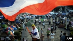 A Thai anti-government protester waves a national flag during ongoing rallies at a protest site at Victory Monument in downtown Bangkok, Jan. 24, 2014.