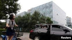2018年8月28日,北京的滴滴出行公司大樓前面,有乘客使用該公司的快車服務。