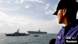 Un marinero filipino ve la llegada del portaviones USS George Washington a Manila, en octubre de 2012. El portaviones arriba este miércoles a Tacloban.