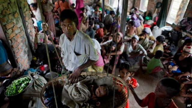 FILE - Internally displaced Rohingya people take shelter in a building ahead of the arrival of Cyclone Mahasen, in Sittwe, northwestern Rakhine State, Myanmar, May 15, 2013.