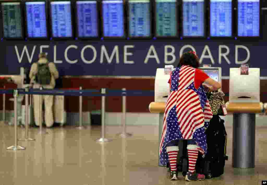 مسافری با لباسی به شکل پرچم آمریکا در فرودگاه بین المللی آتلانتا منتظر پروازش است تا روز شکرگزاری را در کنار خانواده جشن بگیرند.