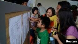印尼亞航失聯班機乘客的家屬在機場查看公告板的消息。