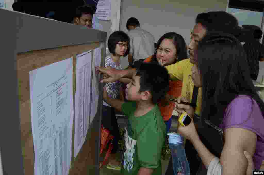 Family members of passengers on board AirAsia flight QZ 8501 look at a passenger list inside a crisis center at Juanda Airport in Surabaya, East Java, Dec. 28, 2014, in this photo taken by Antara Foto.