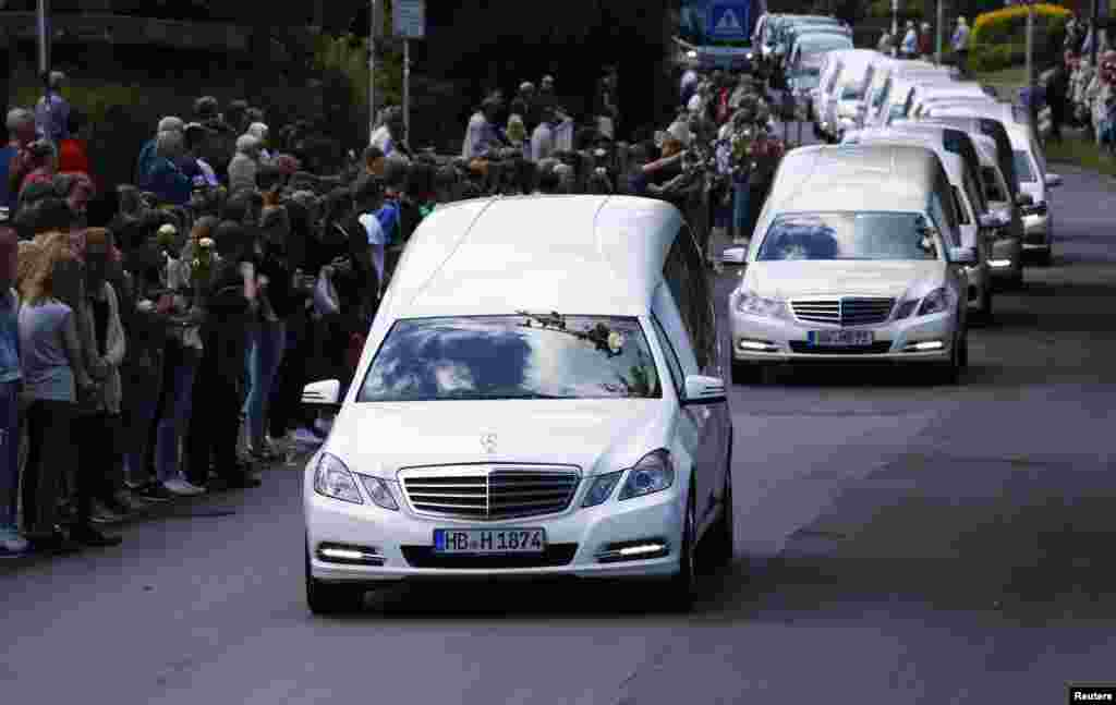 Hearses carrying coffins with remains of victims of the Germanwings flight 4U 9525 plane disaster drive past the Joseph-Koenig-Gymnasium high school in Haltern am See, Germany. Forty four coffins with the victims' remains from the crash on March 24 were flown from France to Germany.