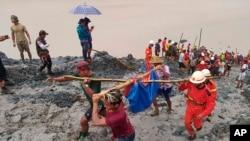 缅甸北部克钦邦帕敢玉石矿区发生山体滑坡,救援人员抬着一具遇难者遗体。(2020年7月2日)