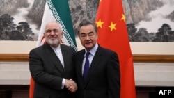 2019年12月31日,中國外長王毅(右)與伊朗外長穆罕默德·賈瓦德·扎里夫(Mohammad Javad Zarif)在北京釣魚台國賓館舉行的會議上握手。