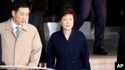 ຜູ້ນຳ ເກົາຫຼີໃຕ້ ທີ່ຖືກຂັບໄລ່ອອກຈາກຕຳແໜ່ງ ທ່ານນາງ Geun-hye, ຂວາ, ເດີນທາງອອກຈາກຫ້ອງການໄອຍະການ ໃນນະຄອນຫຼວງ ໂຊລ. 22 ມີນາ, 2017.