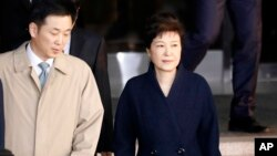 FILE - South Korea's ousted leader Park Geun-hye, right, leaves a prosecutor's office in Seoul, March 22, 2017.