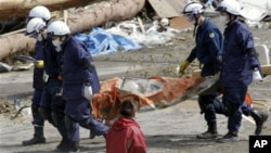 Police officers carry a body during a search and rescue operation in the earthquake and tsunami-devastated city of Rikuzentakata, Iwate Prefecture, northeastern Japan, March 23, 2011.