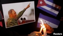 FILE - People place candles beside a picture of Fidel Castro, as part of a tribute, following the announcement of the death of the Cuban revolutionary leader, in Tegucigalpa, Honduras, Nov. 26, 2016.