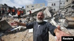 File - A Palestinian man reacts as rescue workers search for victims under the rubble of a house, which witnesses said was destroyed in an Israeli airstrike, in Khan Younis in the southern Gaza Strip, July 2014.