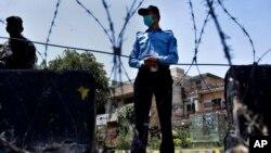 یو پولیس افسر او یو ملېشه عسکر په اسلام آباد کې یو چېک پواینټ سره درېدلي چې د کرونا وبا د خورېدو په مخنیوي کې مرسته وکړي (۱۳ جون ۲۰۲۰)